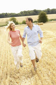 Couple Running Together Through Summer Harvested Field — Stock Photo