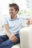 Man Sitting On Sofa Drinking Coffee Relaxing At Home — Stock Photo