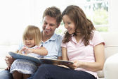 Family Sitting On Sofa Reading Book At Home — Stock Photo