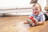 Jovem rapaz brincando com carro de brinquedo de madeira em casa — Foto Stock