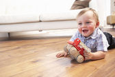 Young Boy Playing With Wooden Toy Car At Home — Stock Photo