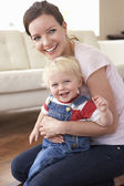 Mother Cuddling Son At Home — Stock Photo