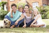 Familjen sitter i trädgården tillsammans — Stockfoto
