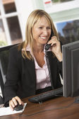 Business woman working on her laptop and talking on the phone — Stock Photo