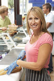 Woman Working Behind Counter — Stock Photo