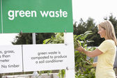 Woman At Recycling Centre Disposing Of Garden Waste — Stock Photo