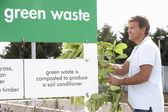 Man At Recycling Centre Disposing Of Garden Waste — Stock Photo