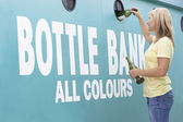 Woman At Recycling Centre Disposing Of Glass At Bottle Bank — Stock Photo