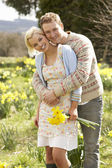 Romantic Couple Walking Amongst Spring Daffodils — Stock Photo