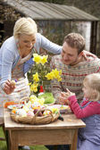 Family Decorating Easter Eggs On Table Outdoors — Stock fotografie