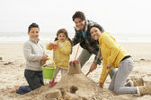 Family Building Sandcastle On Winter Beach — Stock Photo