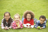 Group Of Children Laying On Grass With Easter Eggs — Stock Photo