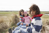 Children Sitting Amongst Dunes On Winter Beach — Stock Photo