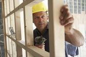 Construction Worker Building Timber Frame In New Home — Zdjęcie stockowe