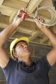 Electricista trabajando en cableado en casa nueva — Foto de Stock