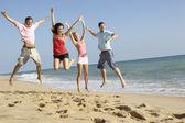 Grupo de amigos disfrutando de vacaciones en la playa — Foto de Stock