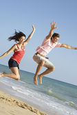 Young Couple Enjoying Beach Holiday Jumping In Air — Stock Photo