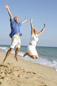 Senior Couple Enjoying Beach Holiday Jumping In Air — Stok fotoğraf