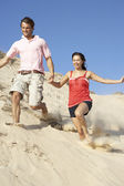 Couple Enjoying Beach Holiday Running Down Dune — Stock Photo