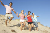 Group Of Friends Enjoying Beach Holiday Running Down Dunes — Stock Photo