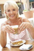 Senior Woman Enjoying Coffee And Cake In Caf — Stock Photo