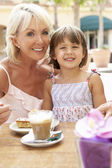 Grandmother With Granddaughter Enjoying Coffee And Cake In Caf — Stock Photo