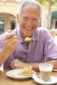 Senior hombre disfrutando de café y pastel en caf — Foto de Stock