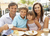 Young Family Enjoying Cup Of Coffee And Cake In Caf — Stock Photo