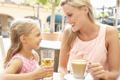Mother And Daughter Enjoying Cup Of Coffee And Juice In Caf — Stock Photo