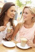 Two Young Women Enjoying Cup Of Coffee In Caf — Stock Photo
