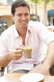 Young Man Enjoying Cup Of Coffee In Caf — Stock Photo