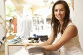 Kadın satış asistanı giyim kasada saklamak — Stok fotoğraf