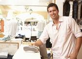 Erkek satış asistanı giyim kasada saklamak — Stok fotoğraf
