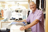 Male Sales Assistant At Checkout Of Clothing Store — Stock Photo