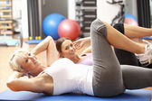 Frauen tun stretching-Übungen im fitness-studio — Stockfoto