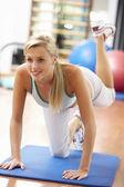 Mujer joven haciendo estiramientos ejercicios de gimnasio — Foto de Stock