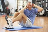 Senior hombre haciendo sit ups en gimnasio — Foto de Stock