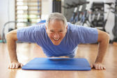 Senior Man Doing Press Ups In Gym — Stock Photo