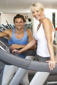 Senior Woman Working With Personal Trainer On Running Machine In — Stock Photo