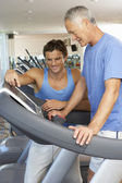 Man Working With Personal Trainer On Running Machine In Gym — Stock Photo