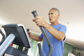 Senior Man On Cross Trainer In Gym — Stock Photo