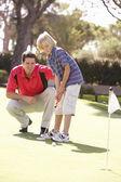 Pai ensinar o filho a jogar golfe no vestir verde — Foto Stock