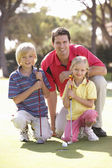 Father Teaching Children To Play Golf On Putting On Green — Stock Photo