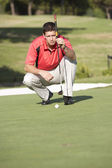 Male Golfer On Golf Course Lining Up Putt On Green — Stok fotoğraf