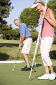 Senior Couple Golfing On Golf Course Lining Up Putt On Green — Stock Photo