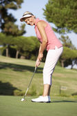Senior Female Golfer On Golf Course Lining Up Putt On Green — Stock Photo