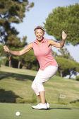 Starszy gracz kobiece na wyciągający putta na zielone pole golfowe — Zdjęcie stockowe