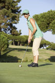 Female Golfer On Golf Course Putting On Green — Stockfoto