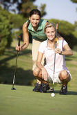 Two Female Golfers On Golf Course Lining Up Putt On Green — Stok fotoğraf