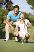 Couple Golfing On Golf Course Lining Up Putt On Green — Стоковое фото